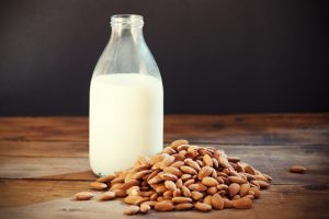 Almond milk in bottle with almonds